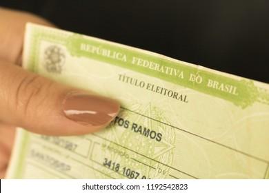"Sao Paulo, Brazil - October 2018: Female hands holding brazilian elector's title voter. (translation: ""Federative Republic of Brazil, voter title)."