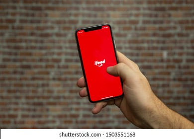 Sao Paulo, Brazil; September 12, 2019: Man holding a Smartphone with ifood logo on it. ifood is a Brazilian company in the segment of food delivery, Brasilian Fintech.