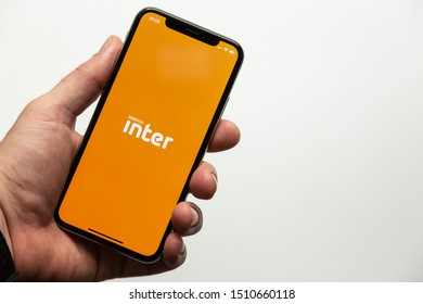 Sao Paulo, Brazil; September 12, 2019: Man holding a Smartphone with Banco Inter logo. Inter Bank is a Brazilian company in the segment of financial services and digital bank.