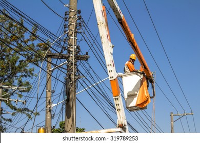 Sao Paulo, Brazil, September 22, 2015. Electrician repair system of electric wire, they wear safety working clothing, climb and work on electric pole of the local utility company
