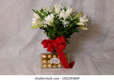 Sao Paulo, SP / Brazil - 26 August, 2017. Ferrero Rocher chocolate with bouquet of white lilies and red bow. Ferrero Rocher is produced by the Italian chocolatier Ferrero SpA.