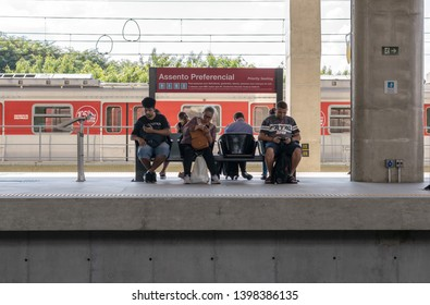 Sao Paulo, SP / Brazil - April 27 2019 - People of great age difference wait for the subway train on a preferential seat while using smartphones cellphones