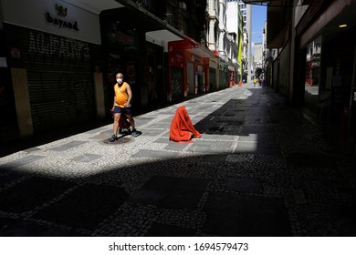 Sao Paulo, SP / Brazil - April 4, 2020: A man walks wearing a face mask to protect from Coronavirus outbreak, COVID-19, next to a homeless person in downtown SP.