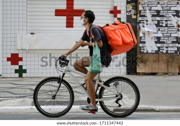 Sao Paulo, SP / Brazil - April 22, 2020: A delivery boy wears a face mask to protect from coronavirus, COVID-19, while ride his bike in front of a drugstore in downtown.