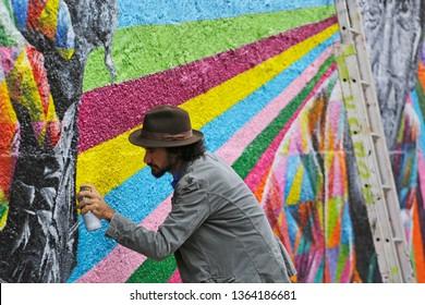 Sao Paulo, SP / Brazil - July 23, 2015: The Brazilian artist Eduardo Kobra use a spray to paint a colorful mural in Vila Madalena neighborhood.