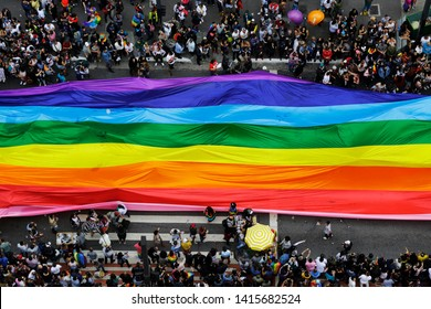Sao Paulo, SP / Brazil - June 3, 2018: Revelers fill the streets holding a giant rainbow flag during the annual gay pride parade in Paulista avenue.