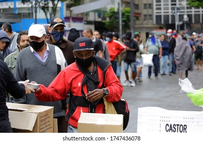 Sao Paulo, SP / Brazil - June 2, 2020: People wait in a big line to receive food donations for lunch in a downtown street during a severe economic crisis due to Coronavirus, COVID-19 pandemic.