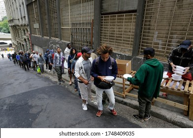 Sao Paulo, SP / Brazil - June 2, 2020: People wait in a big line to receive food donations for lunch in a downtown street during a severe economic crisis caused by Coronavirus, COVID-19 pandemic.