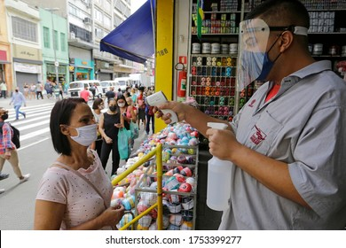Sao Paulo, SP / Brazil - June 10, 2020: A customer has his temperature taken with a non contact infrared thermometer at the entrance of a store in downtown due to Coronavirus outbreak, COVID-19.