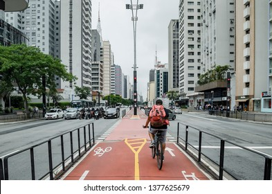 Sao Paulo SP, Brazil - March 01, 2019: Bicycle path of the Paulista avenue (Avenida Paulista). Cyclist riding on the red lanes exclusive for cyclists on the center of the avenue (ciclovia).