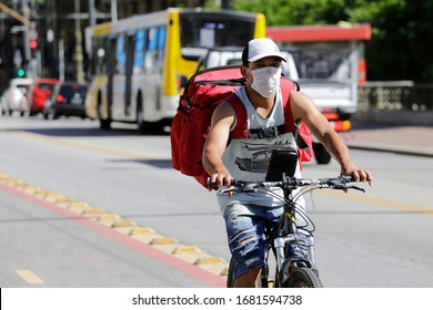 Sao Paulo, SP / Brazil - March 24, 2020: A delivery bike boy wears a face mask to protect from coronavirus, COVID-19, in downtown SP business district.