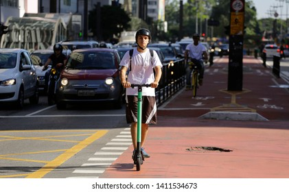 Sao Paulo, SP / Brazil - May 29, 2019: A young man rides a shared electric scooter along the bike path of Paulista avenue, SP business district.