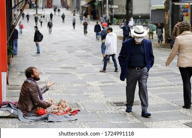 Sao Paulo, SP / Brazil - May 7, 2020: A pedestrian wearing face mask to protect from Coronavirus outbreak, COVID-19, walks by a man begging for money in downtown.