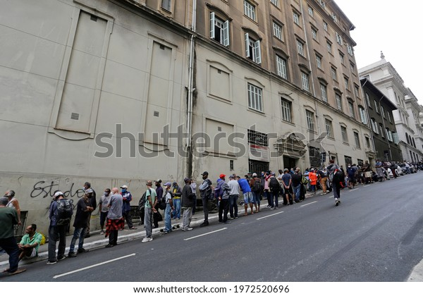 Sao Paulo, SP, Brazil - May 12, 2021: People wait in big line to receive food donations for lunch in a downtown street during a severe economic crisis due to Coronavirus, COVID-19 pandemic.