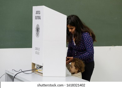 Sao Paulo, SP / Brazil - October 2, 2016: A woman, accompanied by a child, casts her ballot in the municipal elections.