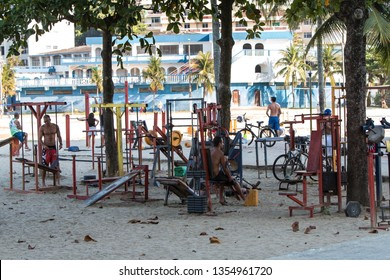 Sao Vicente, Brazil /July 8, 2018:  Men work out with spartan weightlifting equipment in an outdoor gym on a public beach on July 8, 2018 in Sao Vicente, Brazil.