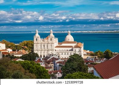 Sao Vicente de Fora Monastery, Alfama District orange rooftops and Tagus River estuary. Lisbon, Portugal.