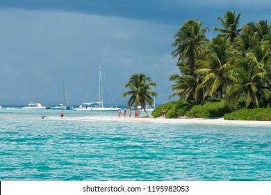Saona island, Este National Park / Dominican Republic - September 11, 2018: People walking along tropical coastline   popular Saona island