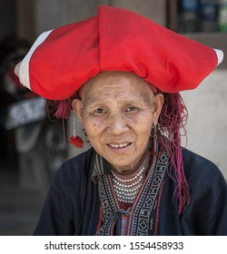 Sapa area, Vietnam. April 26, 2016. Portrait of Vietnamese elderly woman. A woman is dressed in traditional clothing that women wear in Sapa area. On the woman's head is wearing a large red baggy hat.