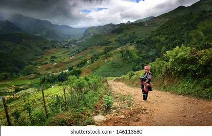 SAPA, Lao Cai, Vietnam - June 11:Rural landscape with an unknown woman with a child of the tribe of the Black H'mong ethnic minority groups. June 11, 2012 Sapa, Vietnam.