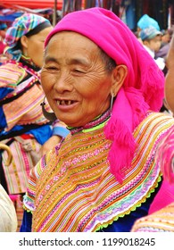 Sapa, Vietnam - April, 2010: Portrait of an elderly woman selling at the market with traditional colorful clothes and pink head scarf. She is almost toothless with bad rest of teeth, wrinkles, smiling