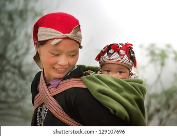 SAPA, VIETNAM -FEBRUARY 11:mother and child Hmong of Sapa on February 11 2012 in Sapa. two-year-old boy named Vangcua.Hmong people are known for their indigo-dyed costumes and ornate silver jewellery