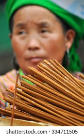 SAPA, VIETNAM - FEBRUARY 22, 2013: Hmong woman selling incense sticks in Bac Ha market. Bac Ha is hilltribe market where people come to trade for goods in traditional costumes