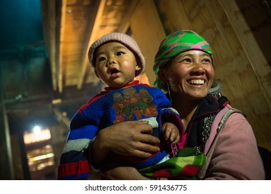 SAPA, VIETNAM - JAN 11, 2014: Local Hmong hill tribe woman poses for portrait with son