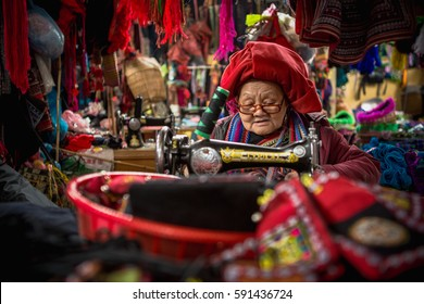 SAPA, VIETNAM - JAN 12, 2014: Unidentified Hmong hill tribe woman uses sewing machine in hill tribe fabric and clothing market