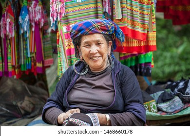Sapa, Vietnam- June 13, 2019: village Cat Cat, Elderly grandmother in national clothes, embroiders patterns on clothes