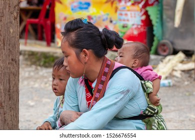 Sapa, Vietnam- June 14, 2019: Sapa of city, Woman with a sick child on his back from Red Dao Minority Group in Sapa, Vietnam