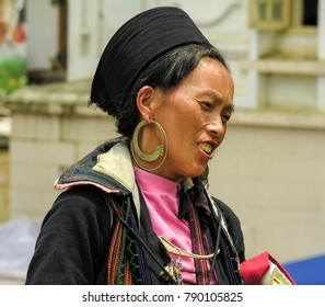 Sapa, Vietnam - June 30 2017: Black Hmong woman traditonally dressed next to market square. Hmong people are one of the local hill tribes.