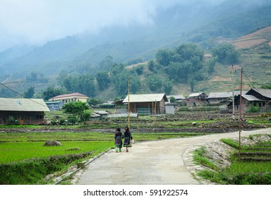 Sapa, Vietnam - May 30, 2016. Hmong girls walking on rural road in Sapa, Vietnam. Sa Pa is a frontier township in Lao Cai Province in north-west Vietnam.