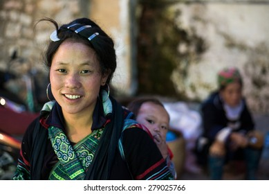 SAPA, VIETNAM - OCTOBER 26 2013: Hmong woman with a child on her back in Sapa on October 26, 2013 in Sapa. Hmong is on of the minority ethnic group living in Sapa in Vietnam.