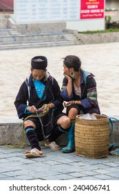 SAPA, VIETNAM - SEP 20, 2014: Unidentified Hmong women in a traditional costume making stuff to sell and offer to tourists Hmong people is a minority ethnic group living in Sapa