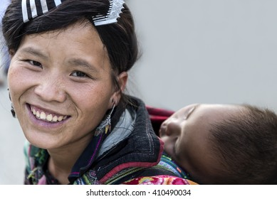SAPA, VIETNAM, September 11, 2014 : Hmong woman hill tribe happy smiling in traditional clothes beautiful costume dress  with her son sleeping