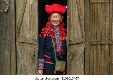 Sapa,Vietnam - April 13, 2018: Portrait of a ethnic woman from Red Dao minority standing in the threshold of her house. She wears traditional and colorful dress and red turban.