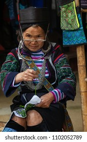 Sapa,Vietnam - April 14, 2018: Traditionally dressed old Woman belonging to Hmong ethnic group in Vietnam sells handicrafts to the tourist in Lao Cai, Sapa, Vietnam.