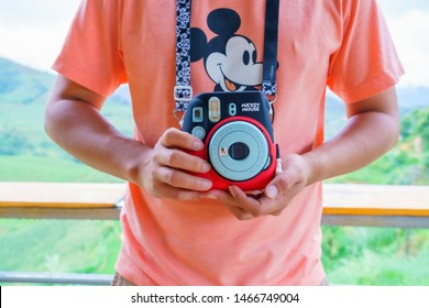 SAPA/VIETNAM - - JULY 15: Fujifilm Instax Mini 9 Mickey Mouse limited edition set Cute camera Start selling first in the world by big camera. on 07 15 2019 Men wearing Orange t-shirts Mickey Mouse.