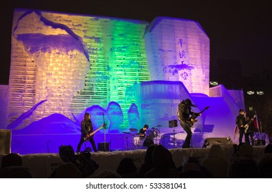 SAPPORO, JAPAN - FEBRUARY 10, 2016: A Japanese rock group performs on a giant ice stage lit with green, purple, and yellow lights in a public park at the international Sapporo Snow Festival.