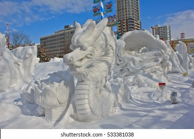 SAPPORO, JAPAN - FEBRUARY 11, 2016: A giant snow sculpture of an angry dragon sits under a blue sky at the international Sapporo Snow Festival.