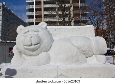 SAPPORO, JAPAN - FEBRUARY 11, 2016: A giant snow sculpture of the teddy bear character Ted, lying lazily on a sofa, sits under a blue sky at the international Sapporo Snow Festival.