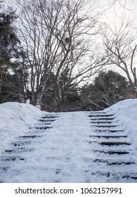 Sapporo, Japan - February 11, 2018: Stairs covered in winter snow at Sapporo Fushimi Inari Shrine, Hokkaido, Japan