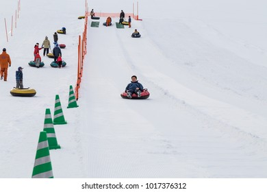 Sapporo, Japan, January 28, 2018: Takino  Suzuran Hillside Park offers family fun activities during winter. Featured here kids having fun in snow boarding on slop.