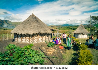 Sara village, Papua New Guinea - July 2015: Native people stand near their house on beautiful sunny day and look to photocamera at Sara village in Papua New Guinea. Documentary editorial.