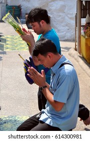 Saraburi, Thailand - January 8, 2013:  Two Thai man holding incense stocks and floral offerings pray at a Wat Phra Phutthabat outdoor shrine