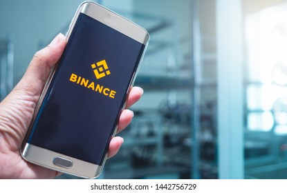 Saraburi, Thailand/ July 2019 :Hand holding mobile on screen logo binance lift up background is blur room  have digital money digger. Concept news about trading web binance of Chinese digital money.
