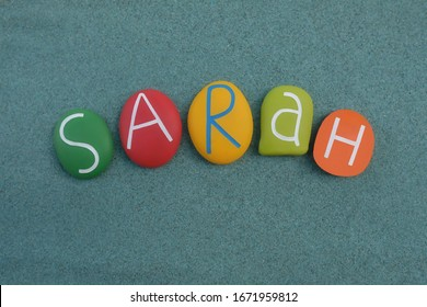 Sarah, female given name composed with multi colored stone letters over green sand