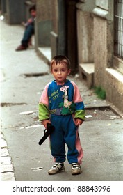 SARAJEVO, BOSNIA, 16 MAY 1993 ---- A young unidentified Bosnian boy plays with his father's army-issued pistol on a street corner in the besieged capital of Sarajevo.