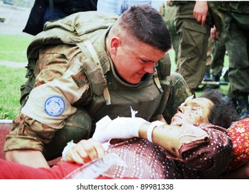 SARAJEVO, BOSNIA - APR 4: An Ukrainian soldier with the United Nations Protection Force (UNPROFOR) in Bosnia helps a wounded woman during the siege of Gorazde at a medical center in Sarajevo, Bosnia, on Monday, April 4, 1994